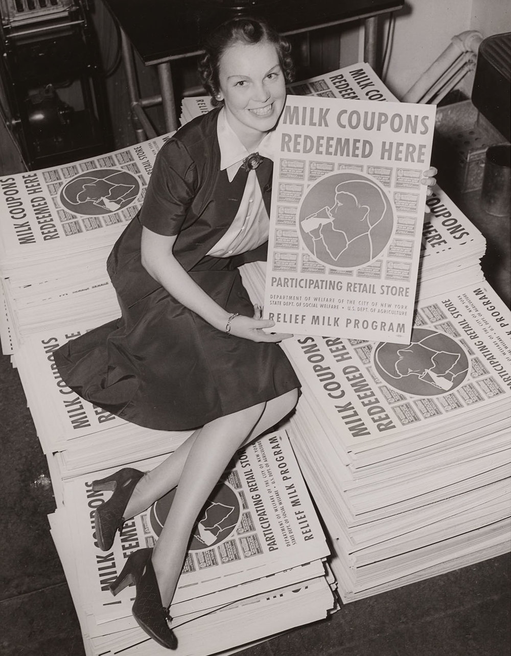 Woman posing with milk relief posters, ca. 1938. WPA Federal Writers' Project Collection, NYC Municipal Archives.