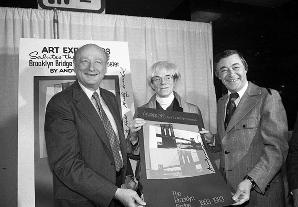 Mayor Edward I. Koch, Andy Warhol, and Brooklyn Borough President Howard Golden holding a poster created by Warhol for the Brooklyn Bridge Centennial, April 5, 1983. The poster was used to promote Art Week and the Fifth Annual Art Expo in New York. Mayor Koch Collection, NYC Municipal Archives.