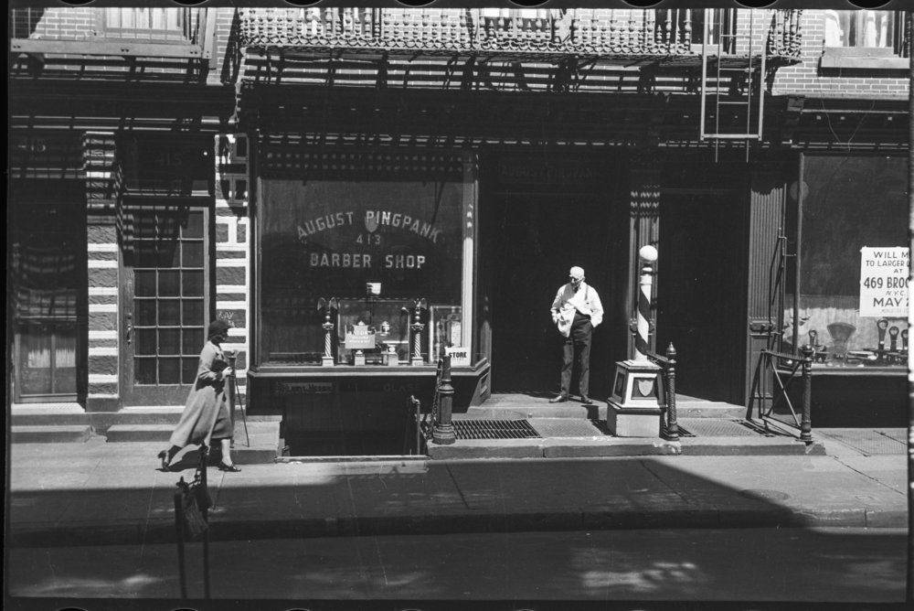 Barber taking a break outside his shop, ca. 1939. Photograph by Clifford Sutcliffe, WPA Federal Writers' Project collection, NYC Municipal Archives.