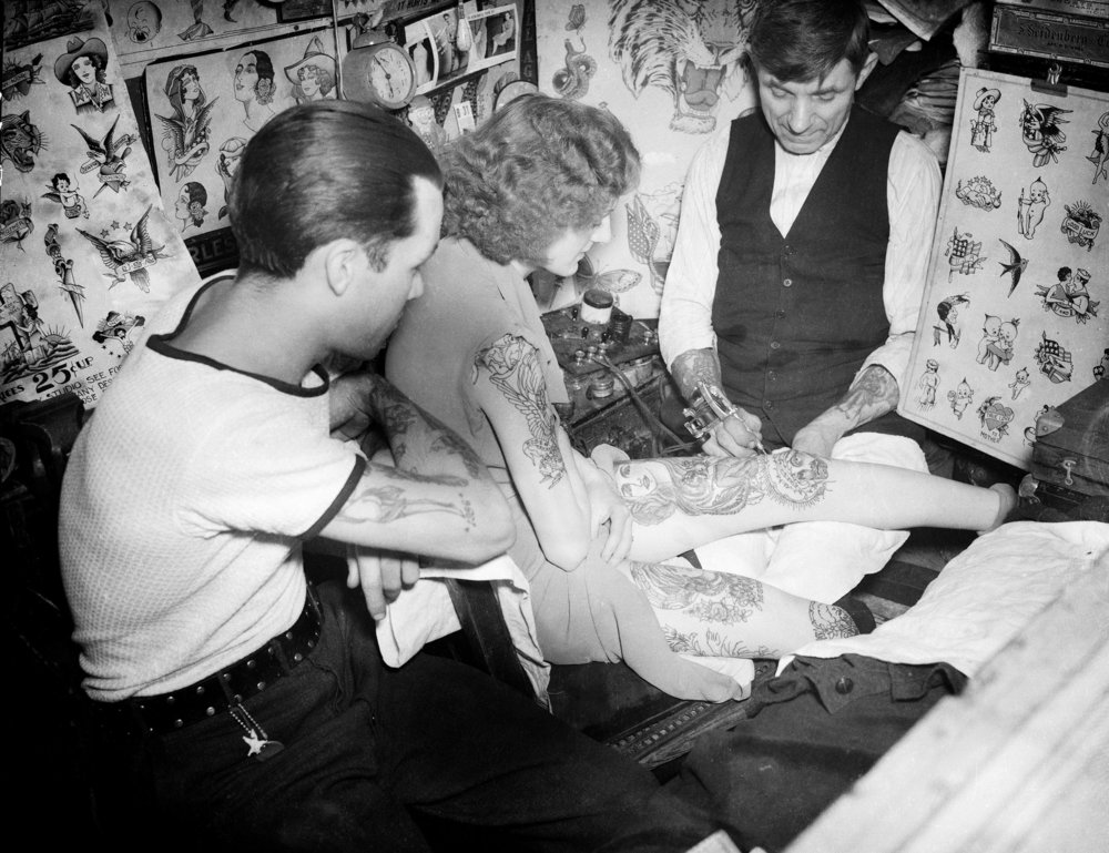 Bowery tattoo artist Charlie Wagner tattooing a woman at his world famous studio at 11 Chatham Square, 1938. Photograph by Daniel Triestman, WPA Federal Writers' Project collection, NYC Municipal Archives.