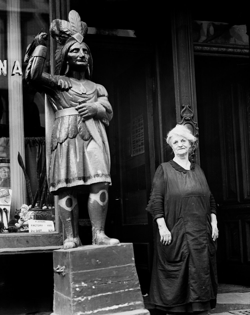 Cigar store owner with wooden Indian, East 7th Street and First Avenue, 1939. Photograph by Sam Brody, WPA Federal Writers' Project collection, NYC Municipal Archives.