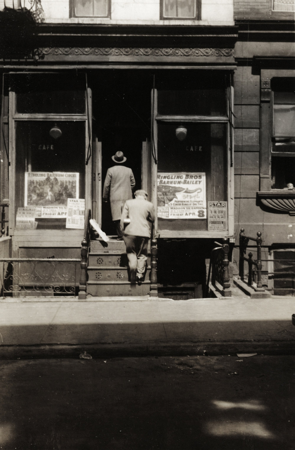 "Two men entering a ""Café"" speakeasy at 11 E. 115th St. at 12:45 p.m. The building had circus posters in the window. NYC Municipal Archives."
