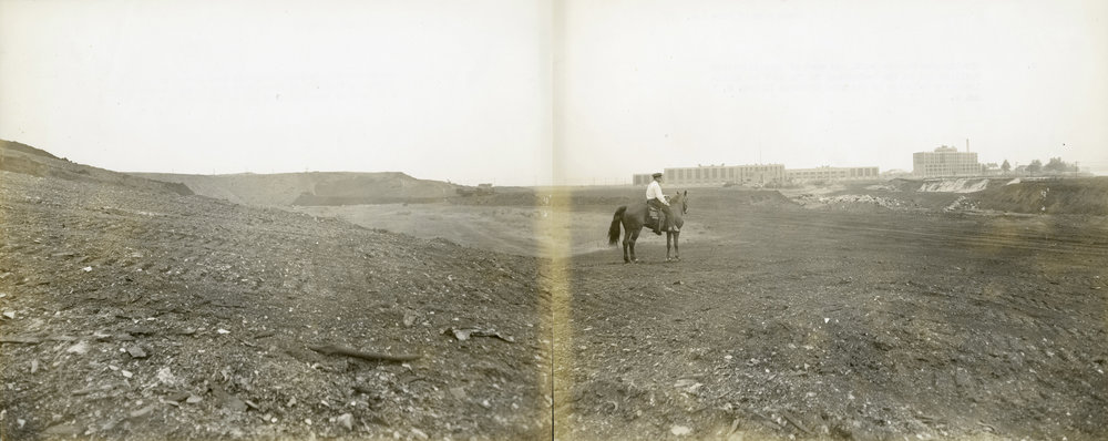 Rikers Island Dump: Guard on horseback looks at Administration and other buildings across graded area, June 1937. NYC Municipal Archives Collection.