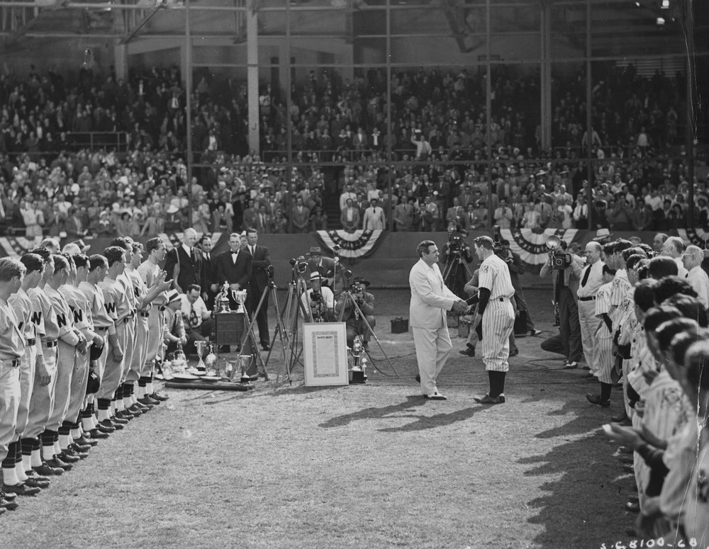 """Babe Ruth shakes the hand of actor Gary Cooper (playing the part of Lou Gehrig) during filming of the movie """"Pride of the Yankees"""" in 1942. The scene is a recreation of """"Gehrig Appreciation Day"""" on July 4, 1939 when Gehrig retired due to his diagnosis with ALS.  Order FHL_0081."""