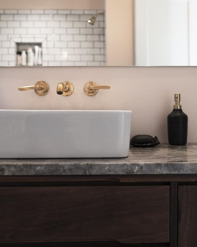 Everyone needs a peaceful spot for those private moments! This was a simple lil bathroom renovation. Moving the plumbing wall left a limited budget for finishes. We worked with the client to source and adapt a mid-century credenza with a vessel sink and remnant stone top, along with a return-discount wall faucet. The brass pulls out the warmth from the wood, stone, and paint. The simple design and warm pink walls help guests feel a little bit of springtime on the dreariest days.