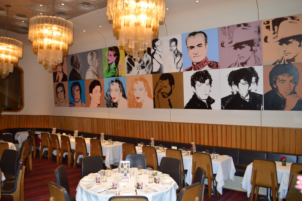 The main dining room of Casa Lever with its series of Warhol's Portraits. On each table, a card of unidentified portraits to facilitate a table guessing game; a completed answer sheet was passed around at dessert. On every menu, Warhol quotations to encourage conversation on Warhol's philosophy.