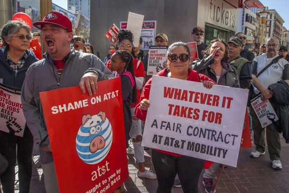 SAN FRANCISCO, CA - Feb. 11, 2017. Workers at AT&T Mobility protest the unwillingness of the company to agree to a new union contract. Members of Communications Workers of America held picket signs, marched and rallied in front of the AT&T Mobility office at the Powell Street cable car turnaround, one of the company's largest consumer offices, in one of the busiest tourist destinations in San Francisco. Photo copyright David bacon.