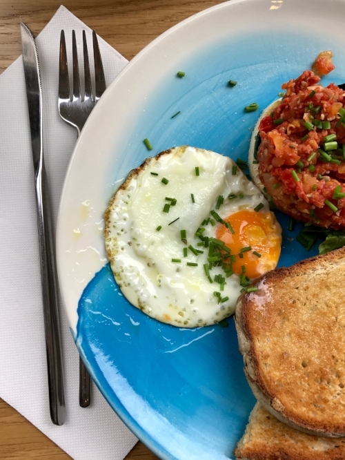 The Breakfast Stack at The Mill: Tomatoes, chorizo and spinach on top of bread with a fried egg, and toast.