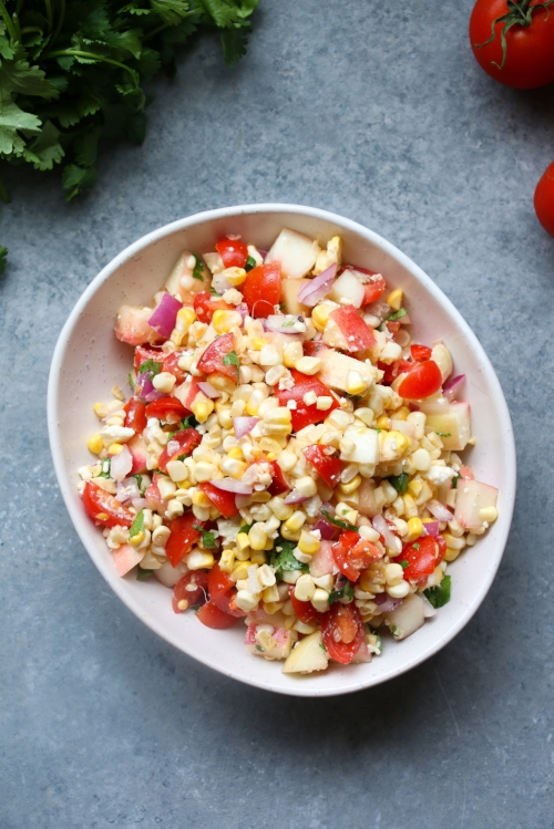 Summer corn salad made with fresh corn, stone fruit, feta, and cilantro.