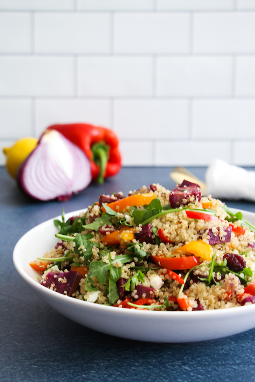 Roasted veggie quinoa salad made with bell peppers, red onion, sweet potato and baby arugula, and topped with a creamy lemon dressing. Vegetarian, and gluten-free.