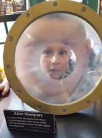 Student peers through an alvin viewport
