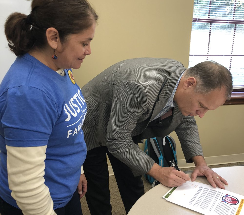 The Reverend Jay Rundell, President of the Methodist Theological School in Ohio, signs the official resolution endorsing the Wendy's Boycott on Tuesday following its unanimous approval by the MTSO Board of Trustees. The CIW's Nely Rodriguez looks on.