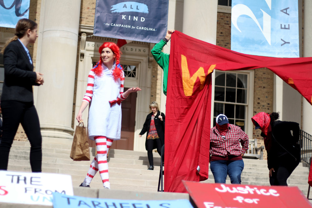 Students at University of North Carolina at Chapel Hill stage a theater skit on the steps of UNC Chancellor Folt's office to highlight the University's complicity in human rights abuses.