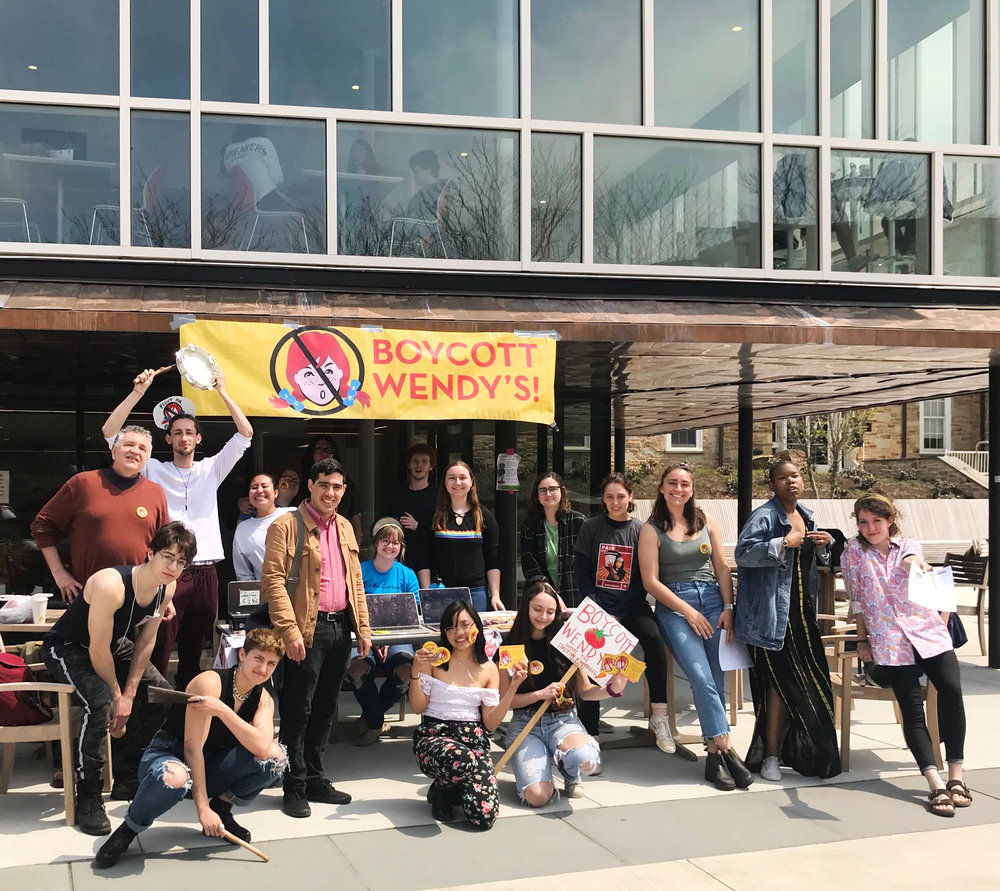 """Students at Goucher College in Baltimore drop a banner from the Mary Fisher Dining Center as part of the Student/Farmworker Alliance's """"Wendy's, We Won't Yield"""" National Day of Action on April 18, 2019."""