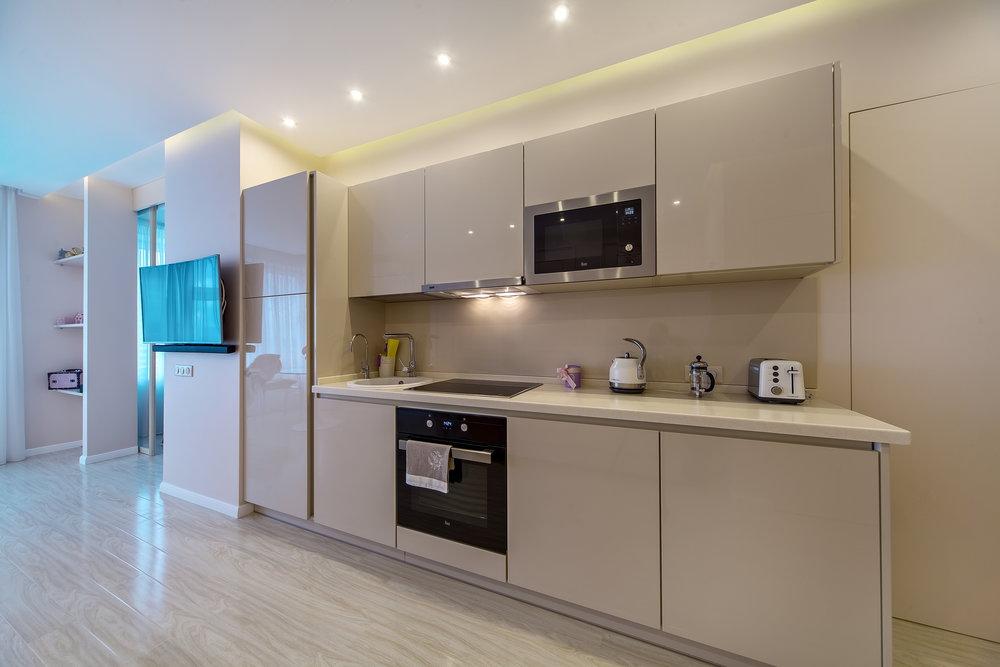 """Гостиная засвечена по периметру, что даёт ощущение ещё более высокого парящего потолка.  Кухня стала частью гостиной, поэтому была выбрана минималистичная мебель в цвет стен, чтобы она """"слилась"""" с пространством, не разбивая его. Отсутствуют даже дверные ручки и ручки у кухонных шкафов (открываются за ниши в фасадах)."""