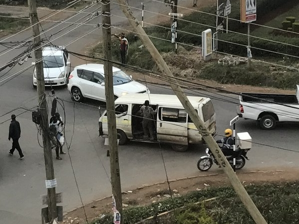 Matatu conductors just hang on in the open doorway