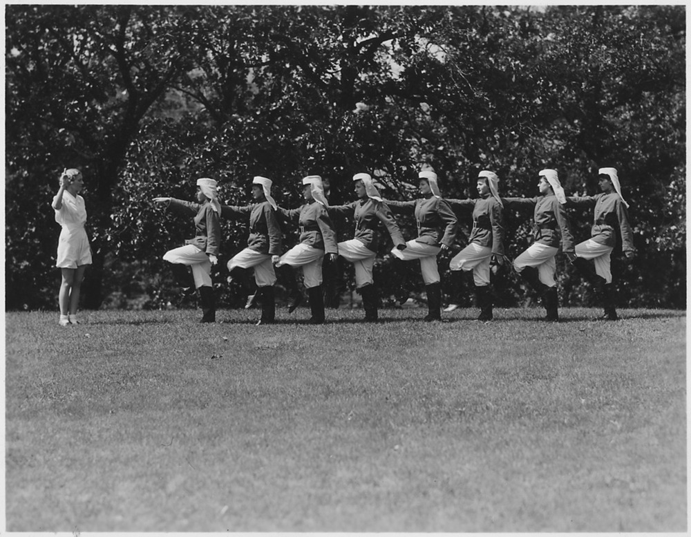 "Workers at a She-She-She Camp partook in group exercises, overseen by staff supervisors.  ("" FERA, Camp for Unemployed Women, Minnesota - NARA - 195641"" by Unknown or not provided - U.S. National Archives and Records Administration. Licensed under Public Domain via Commons "")"