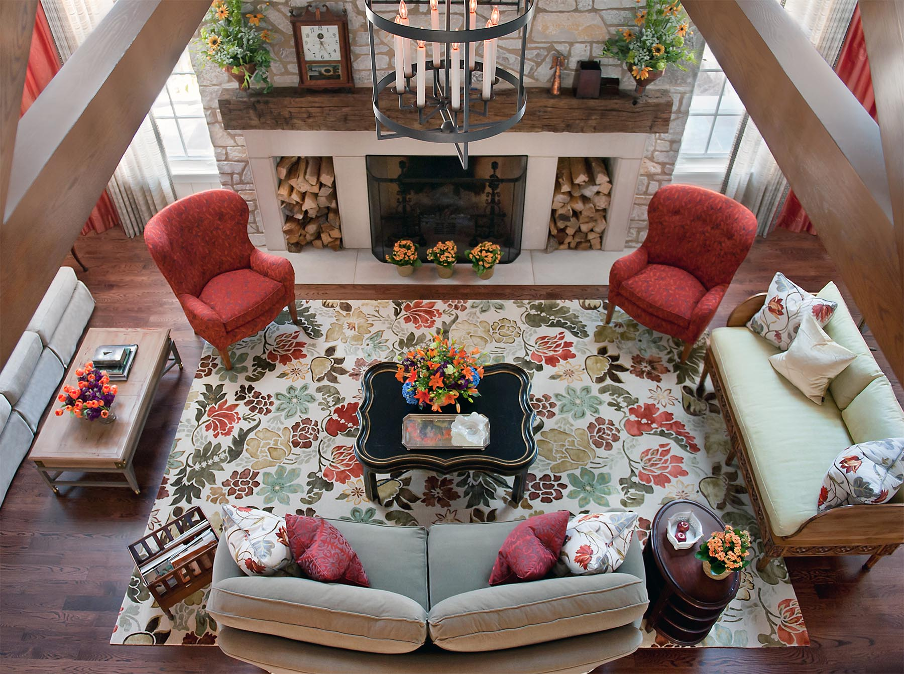 Magnificent aerial view of a cheerful lodge style living room with coral chairs and vibrant floral rug. Come see more interior design inspiration from Elizabeth Drake. Photo by Werner Straube. #interiordesign #classicdesign #traditionaldecor #housetour #elizabethdrake