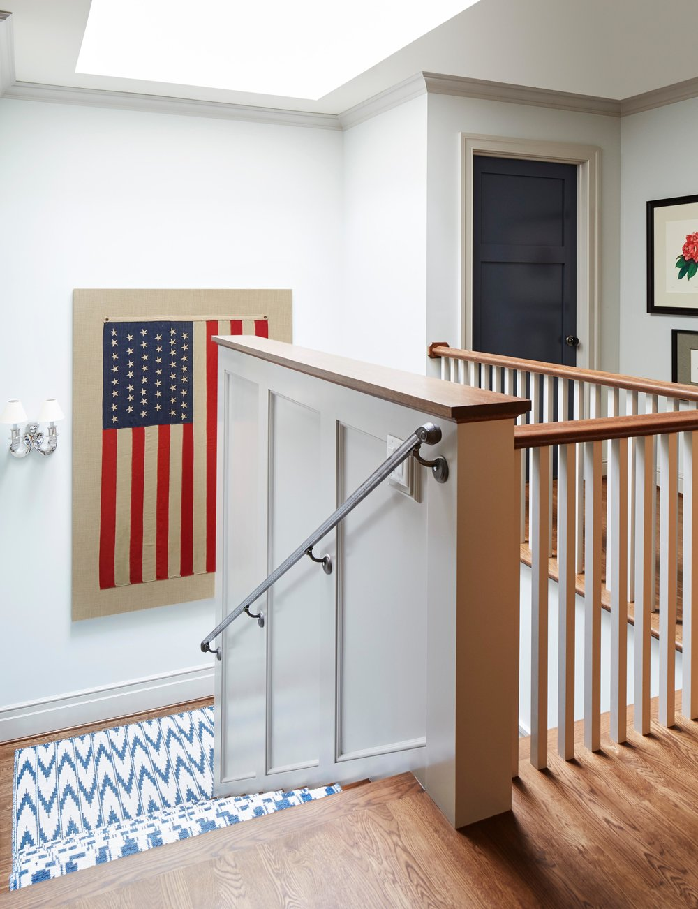 American flag framed on wall near staircase. Come see more interior design inspiration from Elizabeth Drake. Photo by Werner Straube. #interiordesign #classicdesign #traditionaldecor #housetour #elizabethdrake