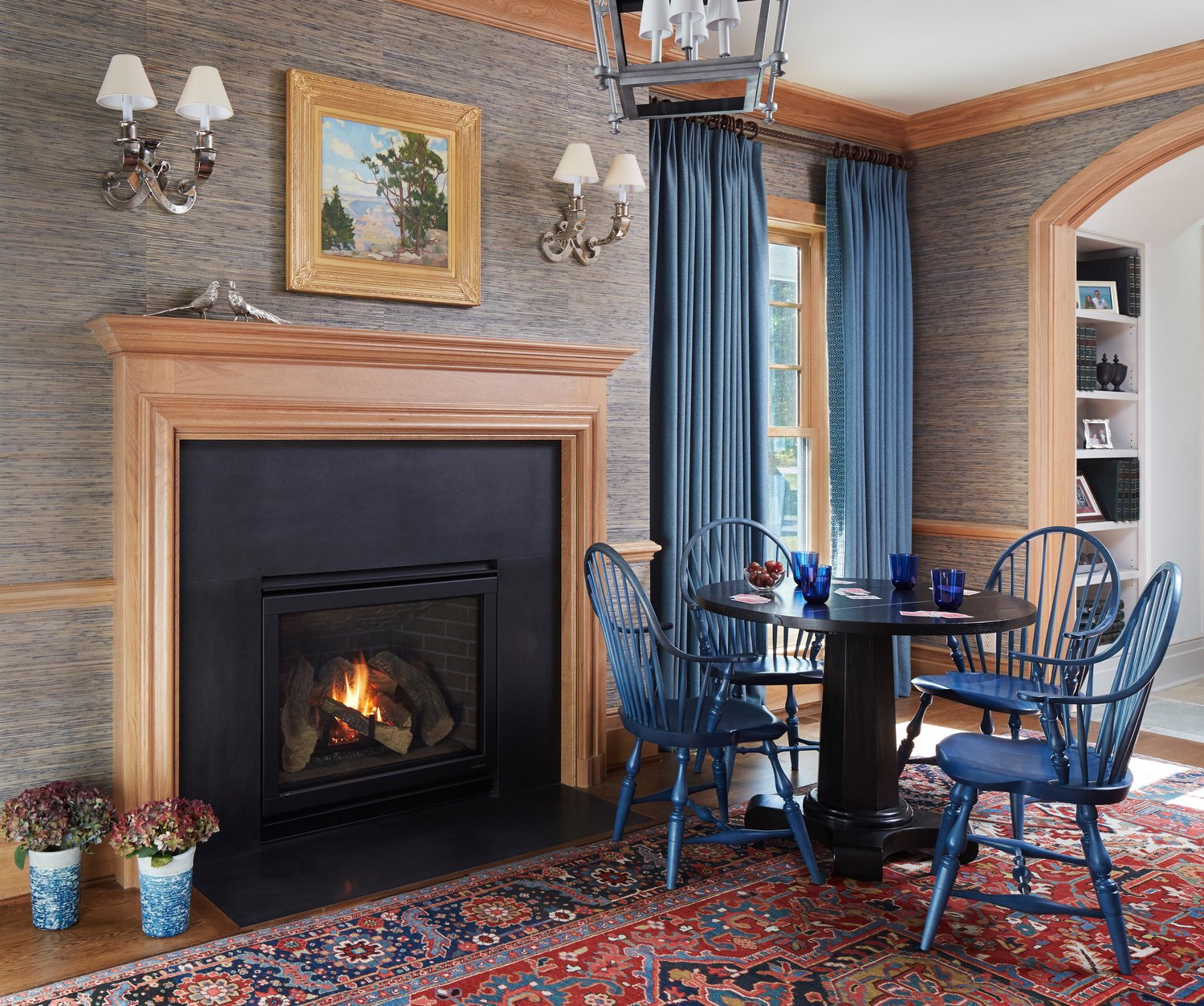 Blue windsor chairs near a cozy fireplace in a family room with grasscloth wall covering. Come see more interior design inspiration from Elizabeth Drake. Photo by Werner Straube. #interiordesign #classicdesign #traditionaldecor #housetour #elizabethdrake