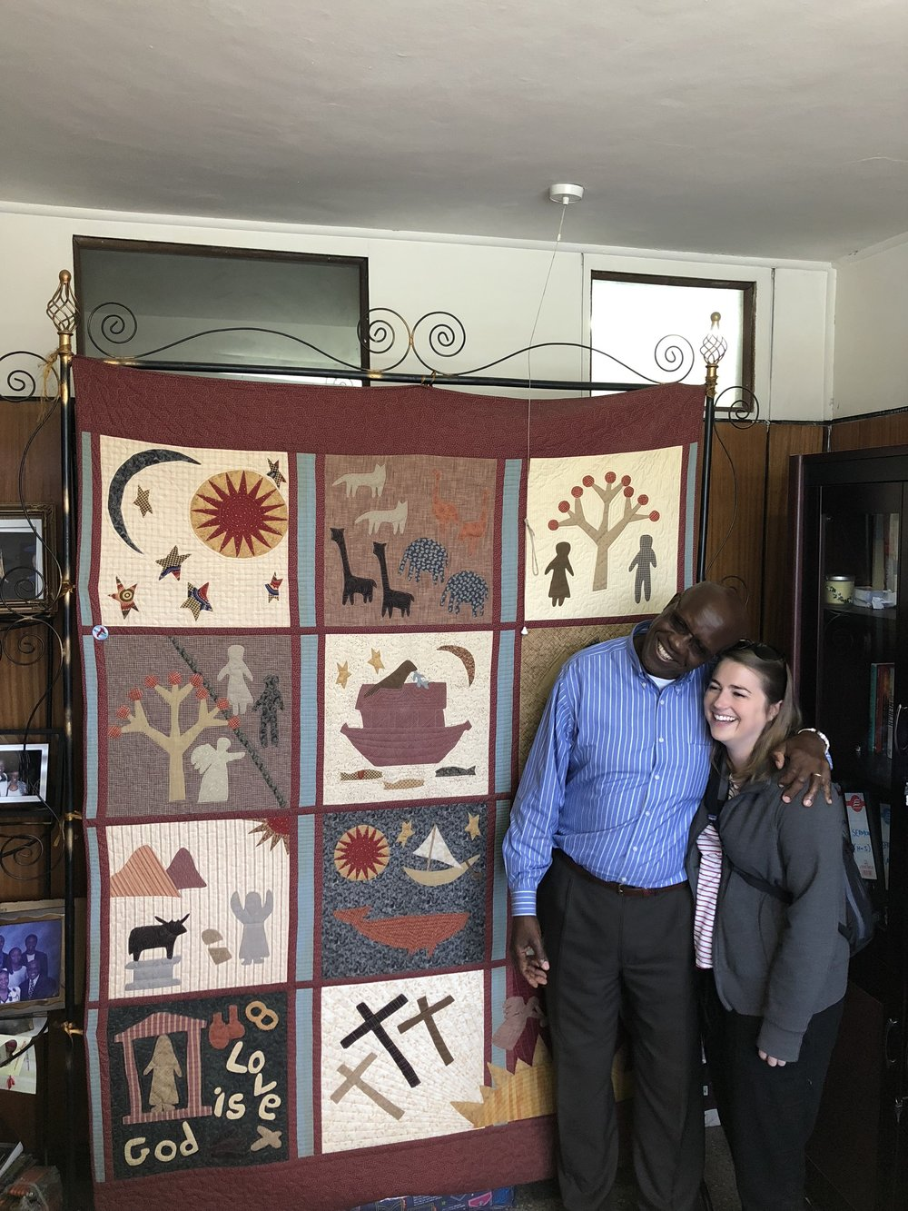 Zablon with Annie in front of the RPC quilt.