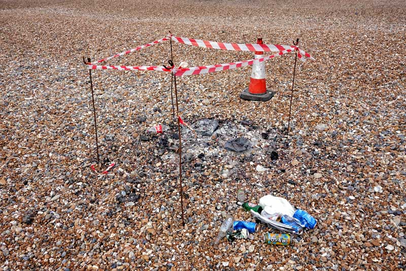body seagull fire roped off rubbish bottles beach