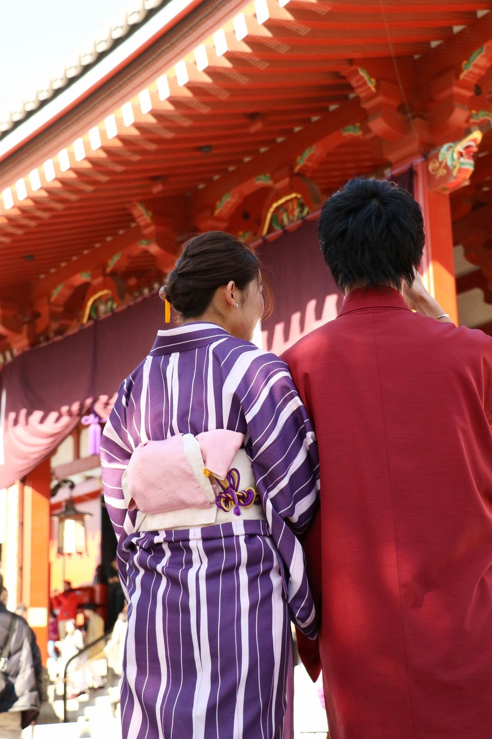 A young couple in traditional Japanese Kimonos walk through Senso-Ji.
