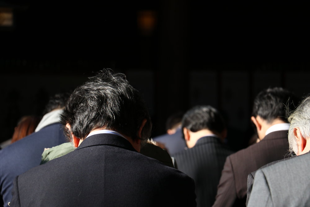 A large corporate group of Japanese men visit Meiji-Jingu shrine.