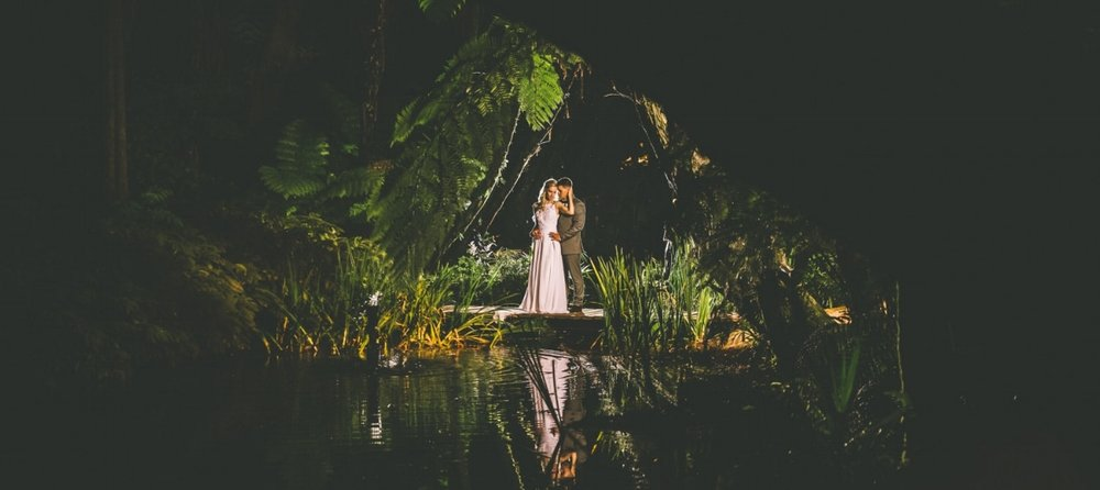 Bride and groom standing by pond at night.jpg