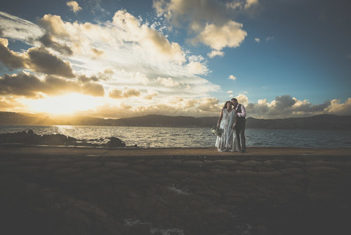 Bride and groom standing on the beach under a sunset.jpg