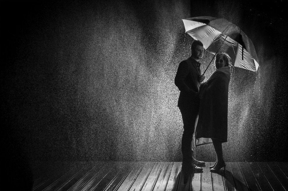 Bride and groom posing with an umbrella in the rain.jpg