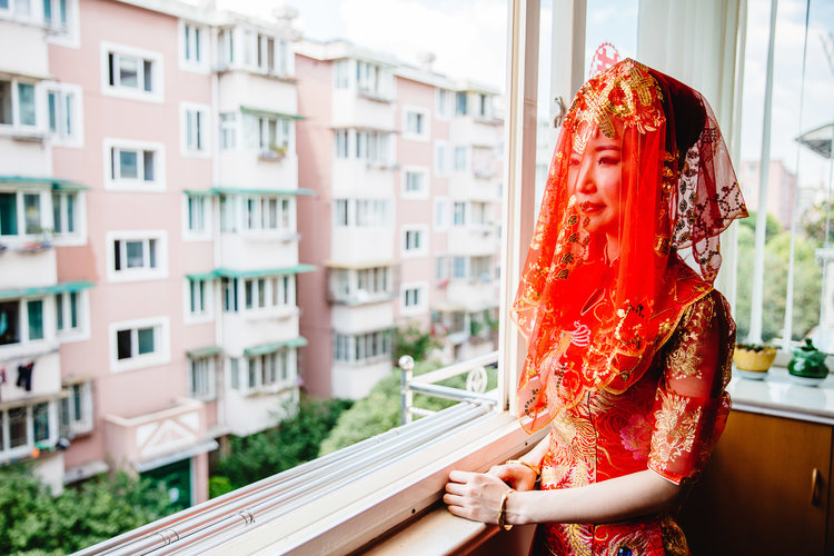 Chinese bride standing by window in a beautiful traditional wedding gown.jpg
