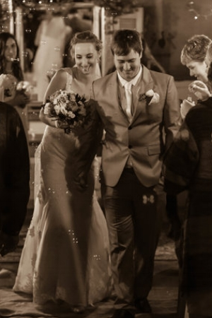 Bride and groom walking up the aisle after the ceremony while guests blow bubbles.jpg