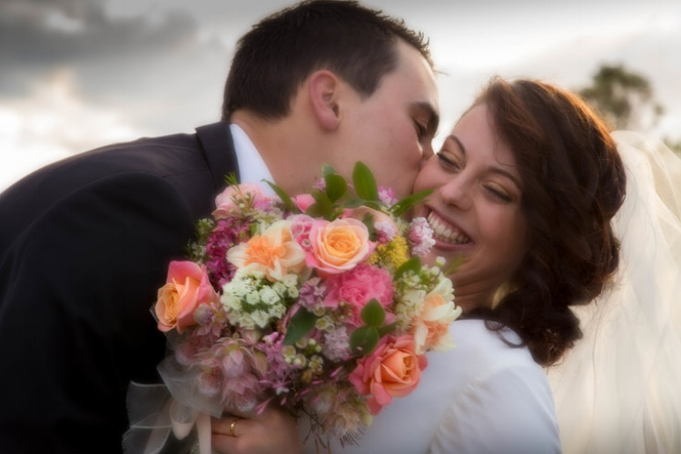 Groom kissing smiling bride on the check while she holds her bouquet.jpg