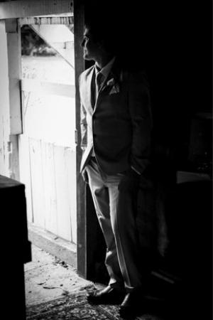 Half dark half light photo of groom standing in doorway.jpg