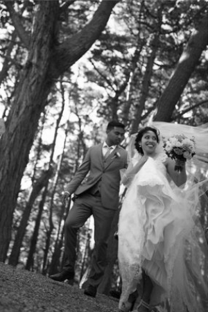 Low angle photo of bride and groom standing in front of the boatshed while it is raining.jpg