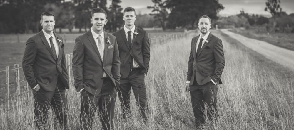 Grooms and groomsmen standing in a field.jpg