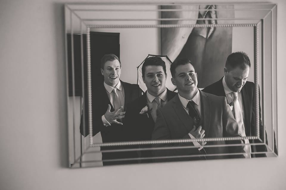 Reflection of groom and groomsmen in mirror.jpg