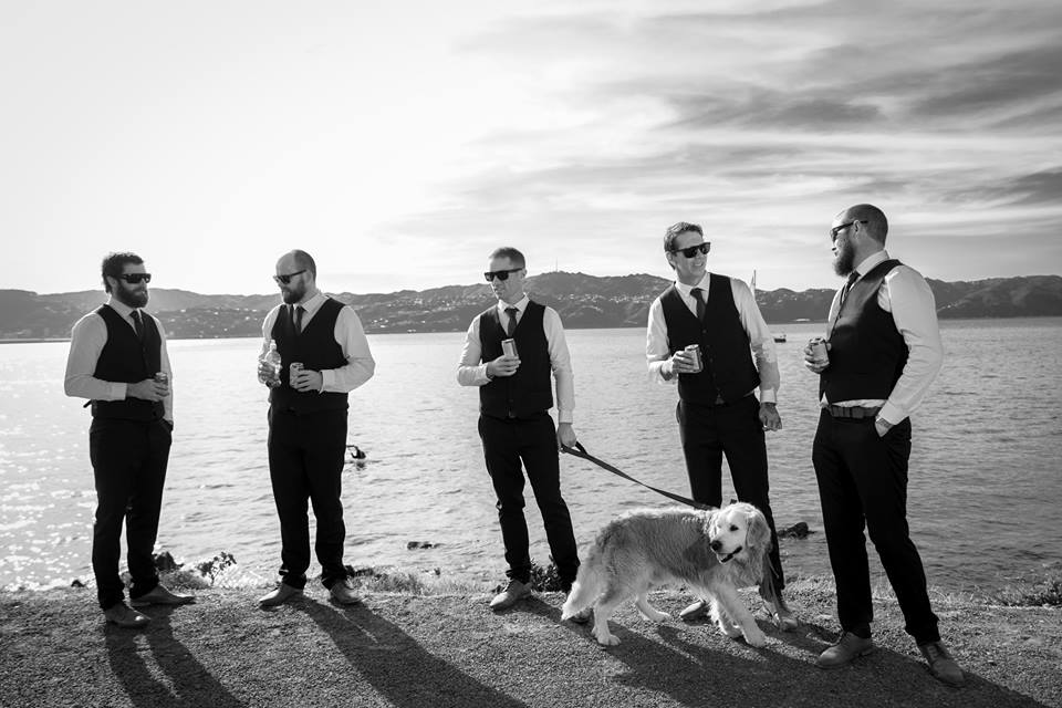 Groom, groomsmen and golden retriever standing on beach holding bears.jpg
