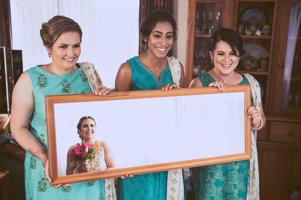 Bridesmaids holding a mirror showing the brides reflection.jpg