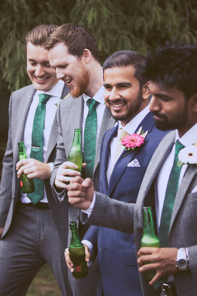 Mid distance shot of groom and groomsmen standing togther drinking a beer.jpg