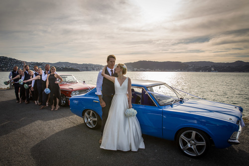 Bride and groom standing in front of blue vintage car with bridal party standing nearby.jpg