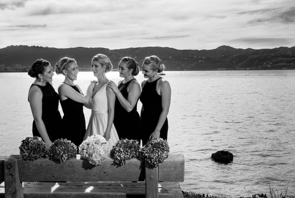 Bride and bridesmaids standing together long Wellington waterfront.jpg