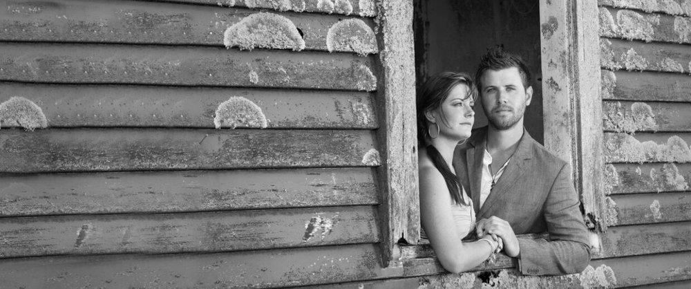 Bride and groom standing in barn window.jpg