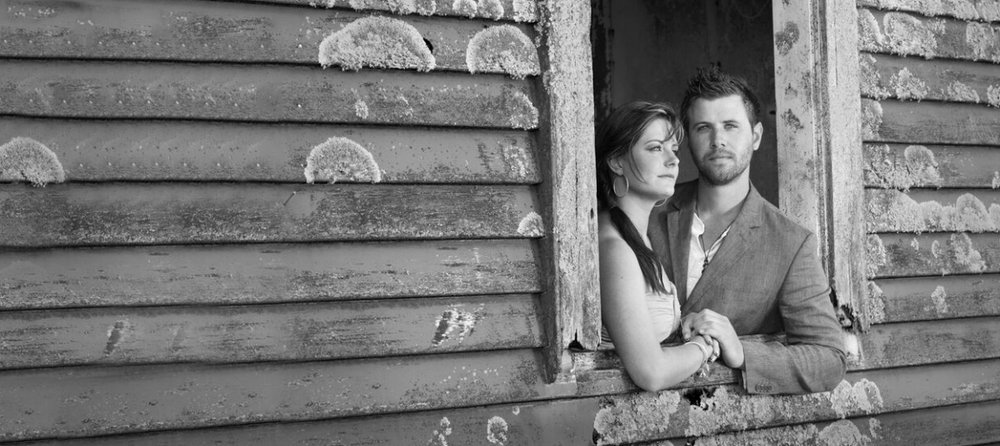 Bride and groom standing in barn window.jpg