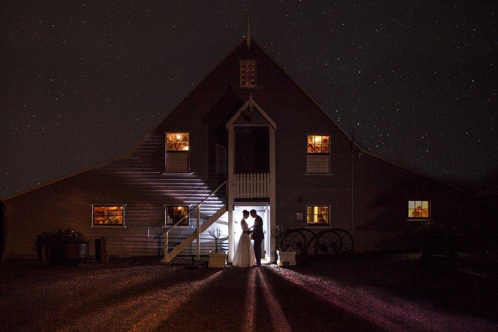Bride and groom standing together in barn doorway under stars.jpg