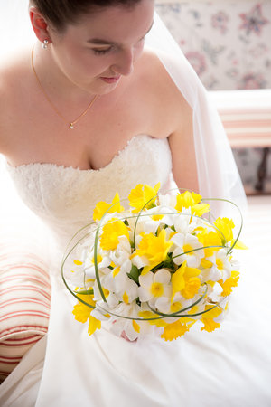 Bright high angle photo of bride sittin on chaise holding yellow and white flowers.jpg