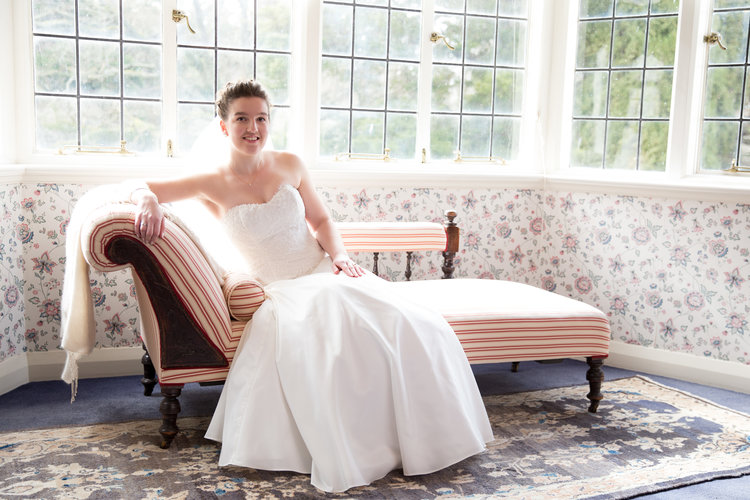 Mid view shot of bride sitting on antique chaise.jpg