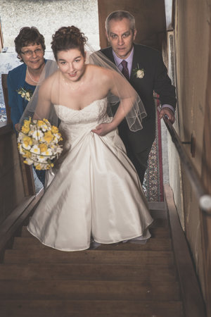 High angle photo of bride walking up stairs with her parents.jpg