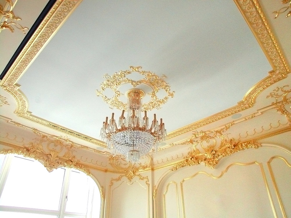 Simple plaster ceiling adorned with many ornamental elements using gilded plaster